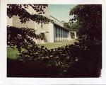 A view of O'Hare Academic Center through bushes by Joseph Souza